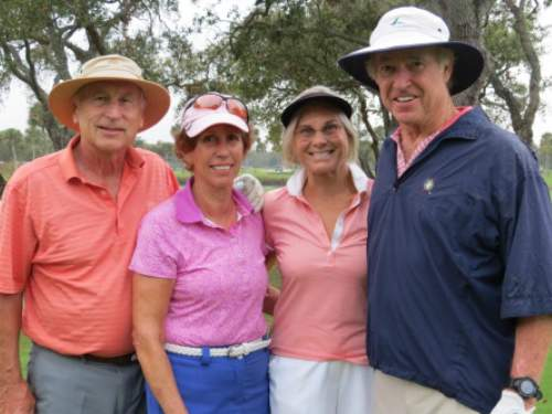 Four adults at golf tournament